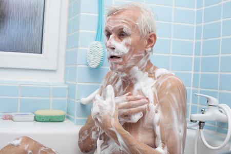 Senior man washing his body with soap in bath. photo