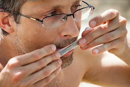 hashish: Close up of man rolling hashish joint. Stock Photo