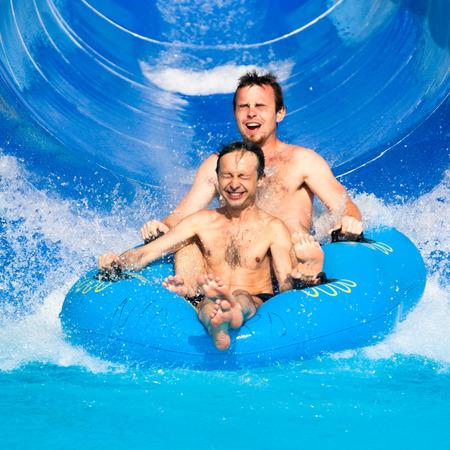 People having fun, water sliding at aqua park. photo