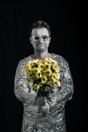 weirdo: Portrait of happy spaceman holding flowers.