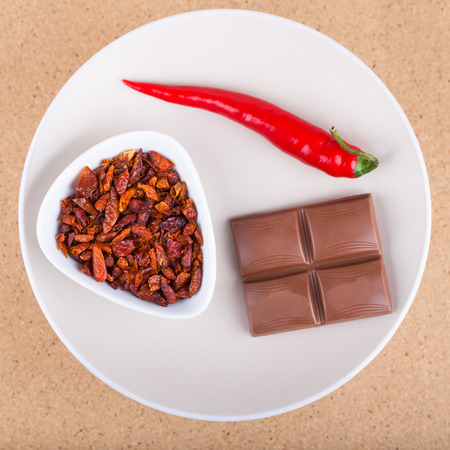 red chilly: Red hot chili peppers with chocolate on plate, over light wooden background.