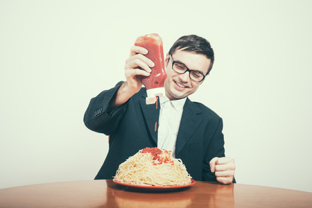 consumerist: Happy consumerism concept. Happy businessman pouring ketchup on huge dish of pasta.