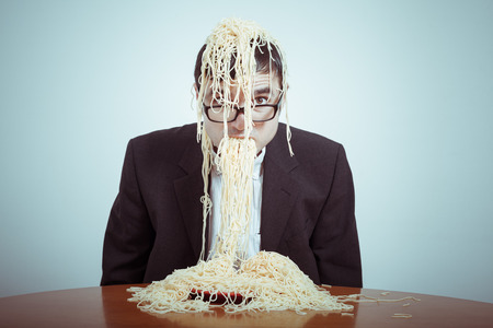 indulging: Overeating and consumerism concept. Nasty businessman eating pasta.