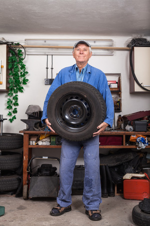 Portrait of happy senior worker changing tire in the garage. photo