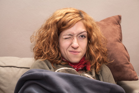 one eye closed: Closeup of a redhead woman face with one eye closed, relaxing on the sofa at home.