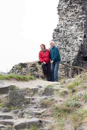 Happy senior couple hiking and resting on rocky trail outdoors. photo