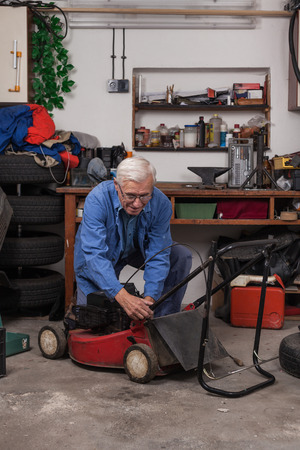 mower: Senior worker maintaining his lawn mower in the workshop.
