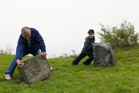 niño empujando: Hombre mayor y un niño niño tratando de mover grandes rocas al aire libre.