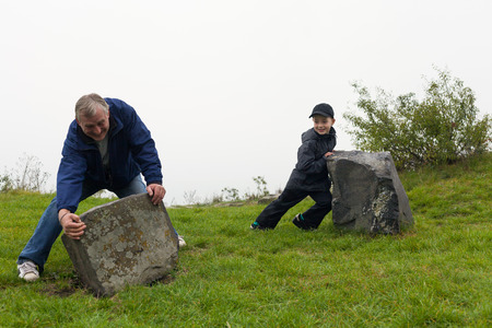 Senior man and child boy trying to move big boulders outdoors.