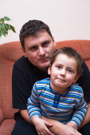 single parents: Portrait of father and his child boy, sitting on sofa at home