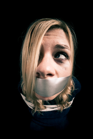 torment: Kidnapped woman hostage with tape over mouth and tied up with rope