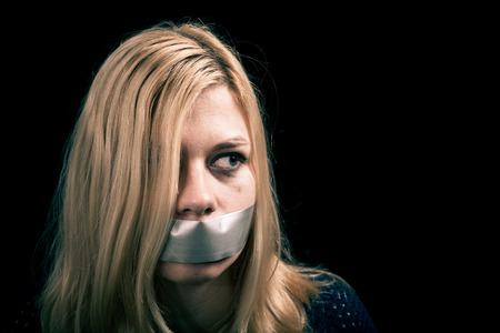 kidnapped: Portrait of scared kidnapped woman hostage with tape over her mouth