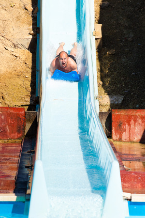 water park: Man having fun, sliding at water park.