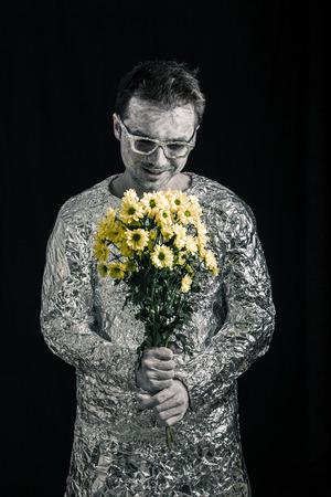 weirdo: Portrait of satisfied spaceman holding flowers.