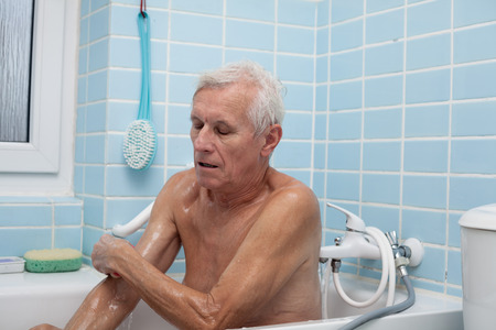 persona de la tercera edad: Hombre mayor de lavar su cuerpo con una esponja de jabón en el baño.