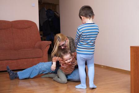madre soltera: Los niños felices y mujer que se divierten en el hogar