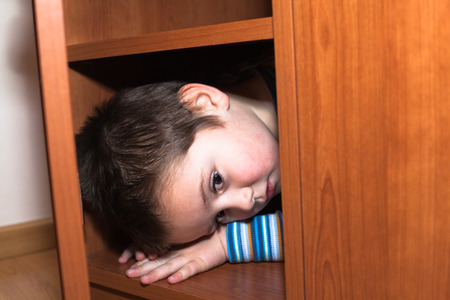 baby wardrobe: Scared child boy hiding in wardrobe