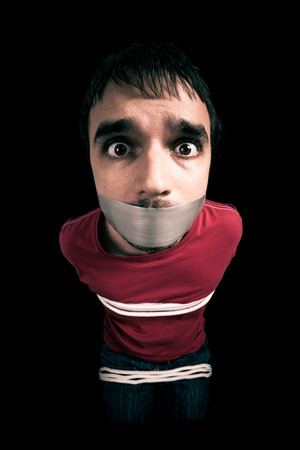 kidnapped: Kidnapped man hostage with tape over mouth and tied up with rope Stock Photo
