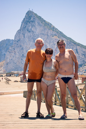 Portrait of two senior men and middle aged woman posing for photo on the beach with Gibraltar rock on the background.