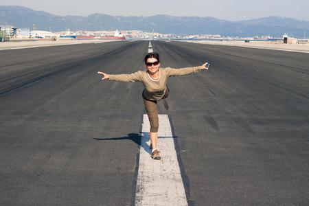 imitating: Happy woman tourist imitating airplane at the airport runway.