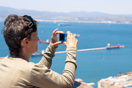 compact camera: Middle aged woman taking photos using compact camera.