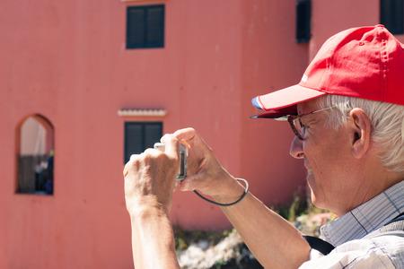takes: Senior man tourist taking photos using compact camera.