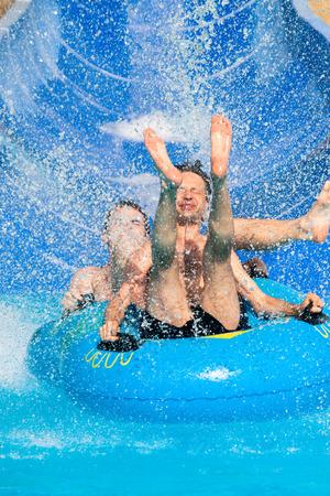 Two men having fun, people water slide at aqua park. photo