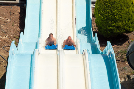 sliding: People having fun, sliding at water park.