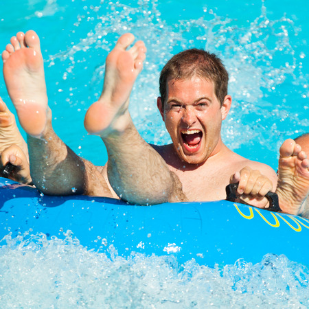 sliding: Man having fun, sliding at water park.