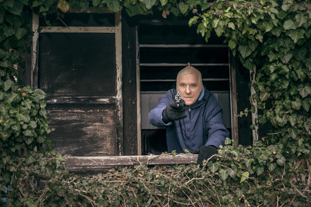 criminal defense: Masked senior escapee man aiming a gun, hiding on overgrown porch of old cabin.