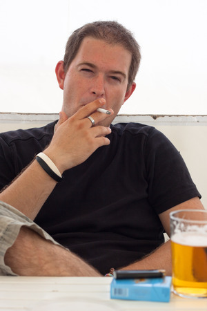 booze: Close up of young man smoking cigarette.