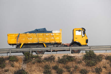 dumptruck: Yellow dump truck on the road with grey sky.