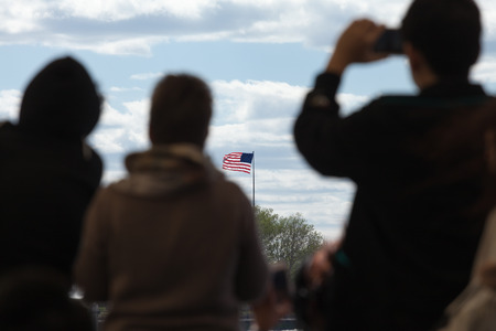 refugees: Silhouettes of travelers looking at the flag of the United States of America.