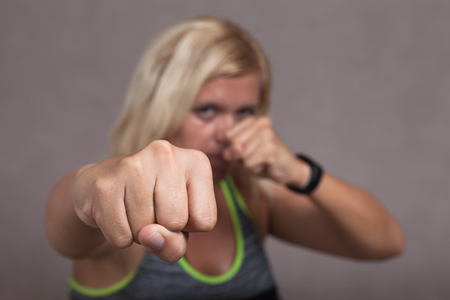 martial law: Dangerous female fighter posing, focus on the fist. Stock Photo