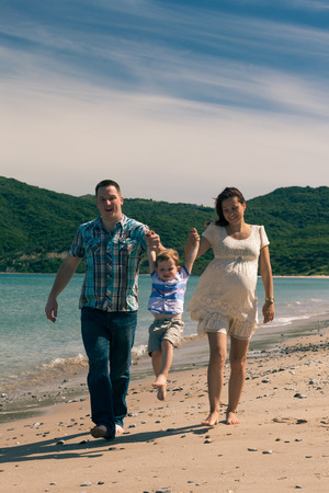 Happy pregnant couple and their son enjoying sunny day, jumping and walking on the coast in Spain. photo