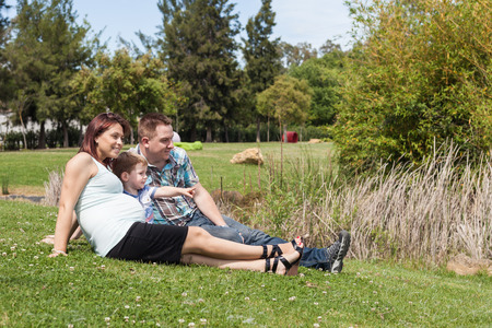 Young happy pregnant family relaxing in the park and enjoying summer day outdoors. photo