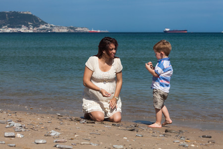 Happy pregnant woman playing with child boy and enjoying sunny day on the beach in Spain. photo