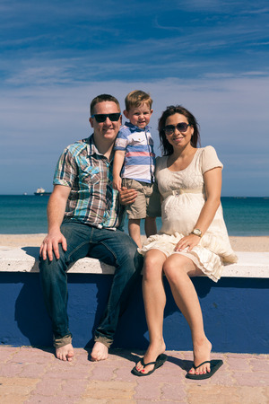 Happy pregnant couple and their son enjoying sunny day on the coast in Spain. photo