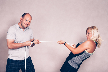 bald girl: Positive confident sporty man and woman pulling a rope. Competition, confidence and effort concept. Stock Photo