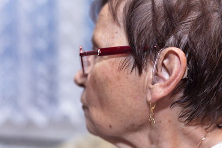 hearing aid: Profile of a senior woman with hearing aid.