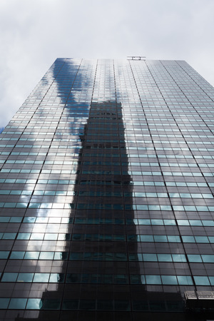 manhattan mirror new york: Low angle view of a skyscraper with glass windows and reflections in Manhattan, New York City.