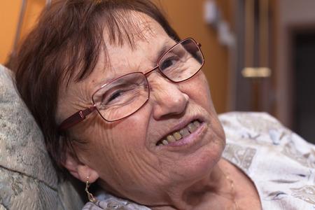 mujer fea: Primer plano de una mujer mayor que hace muecas y frunciendo el ceño.