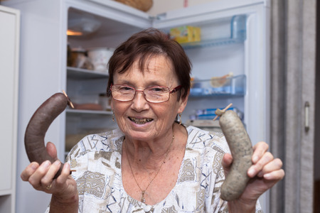 czech women: Happy senior woman holding pork liver sausages while standing in front of the open fridge in the kitchen.