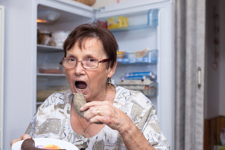 czech women: Senior woman going to eat pork liver sausage while standing in front of the open fridge in the kitchen.