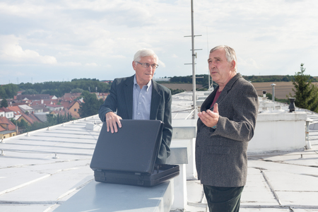 Two senior businessmen with briefcase discussing business deal outdoors on the roof of a building. photo