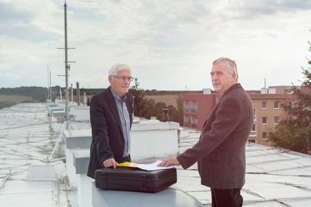 Two senior businessmen with documents making a business deal outdoors on the roof of a building. photo