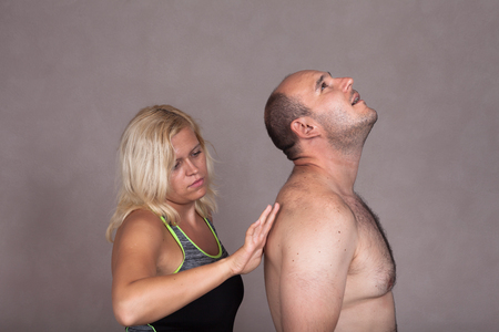 Profile of blonde woman giving a back massage to shirtless man. photo