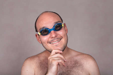 Closeup of funny naked man in swimming goggles daydreaming and looking at you. photo