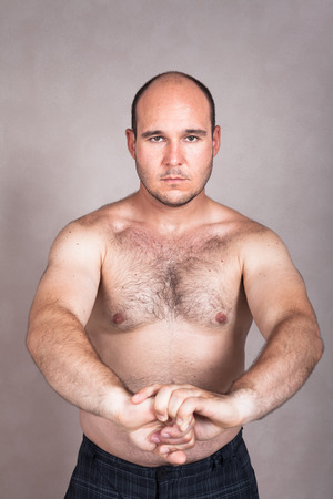 Portrait of serious shirtless man posing and showing his strong body. photo