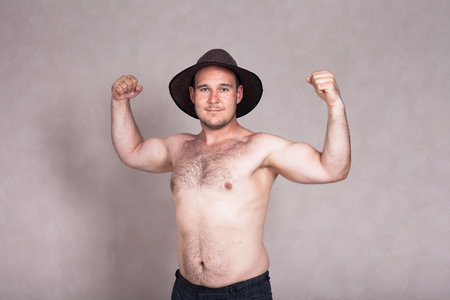 hairy arms: Shirtless man in hat posing and showing his strong arms and hairy body.